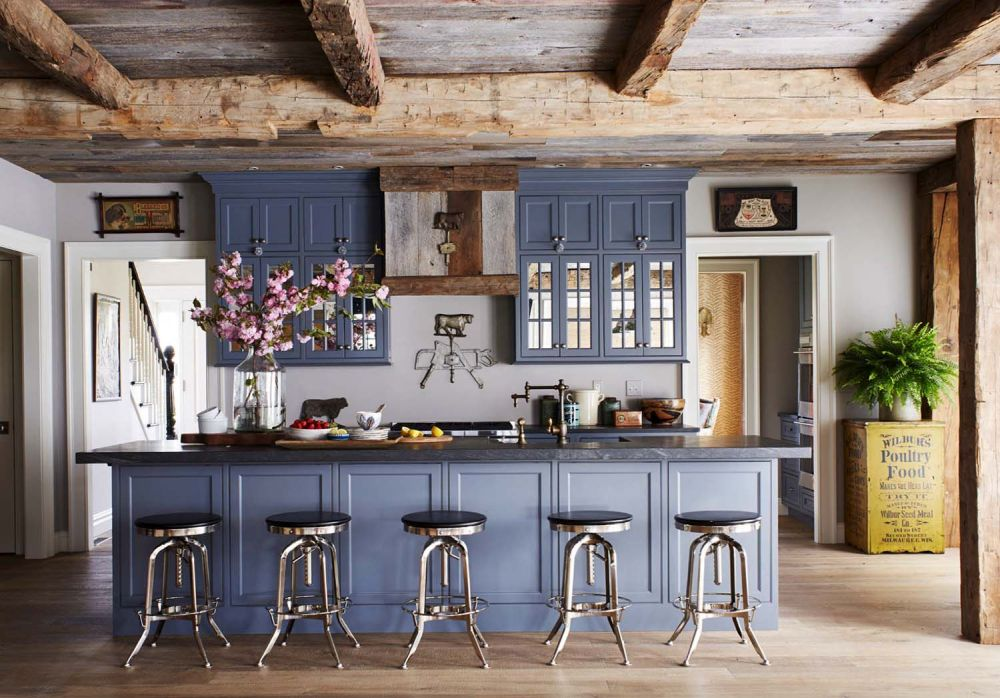 The open space kitchen features a large island which doubles as a bar, complemented by five simple bar stools