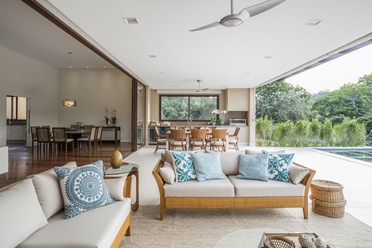 The poolside deck and adjacent area are treated as seamless extensions of the indoor living room