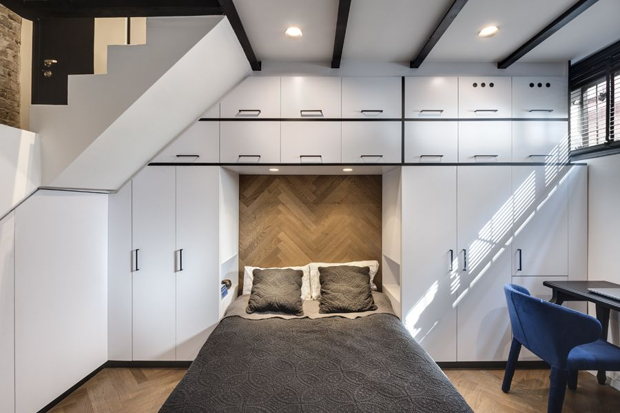 The bed is framed by custom-built white cabinetry which offers lots of storage