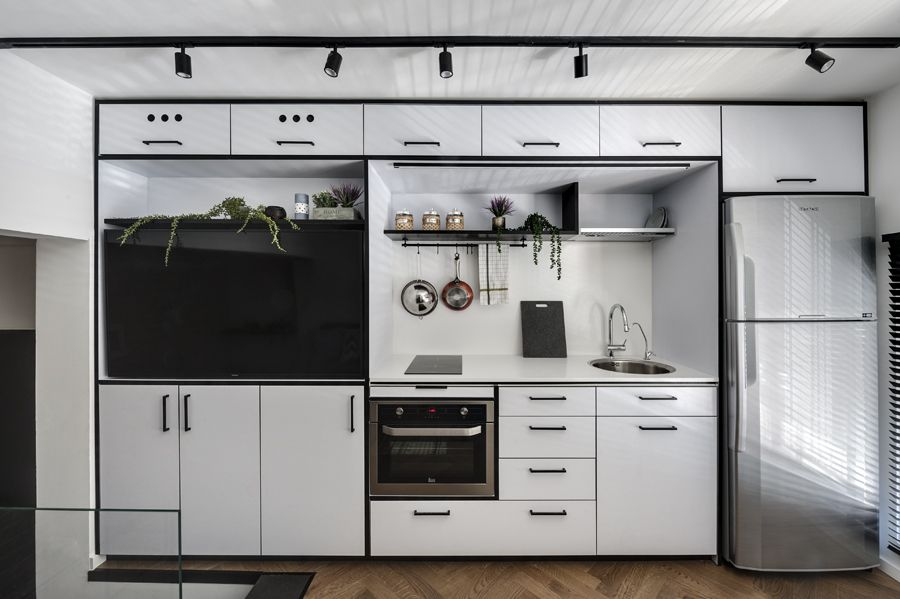 The storage wall includes the kitchen module as well as a large built-in TV