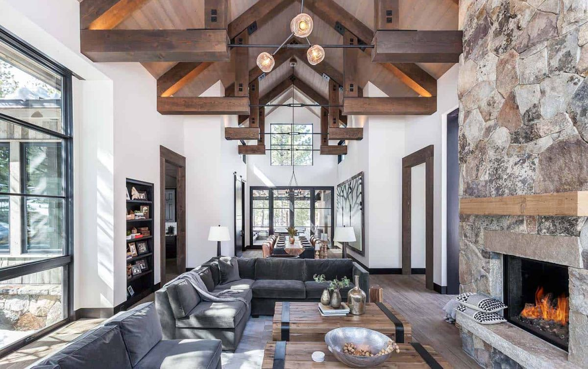 The stone fireplace and wooden ceiling add texture to the decor and create a cozy, rustic vibe