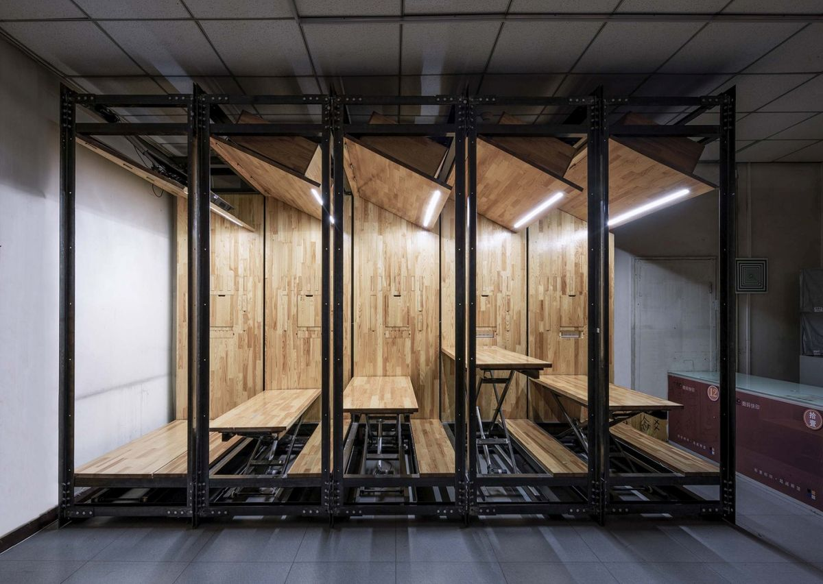 Each desk has a corresponding storage cabinet above it, with built-in lighting