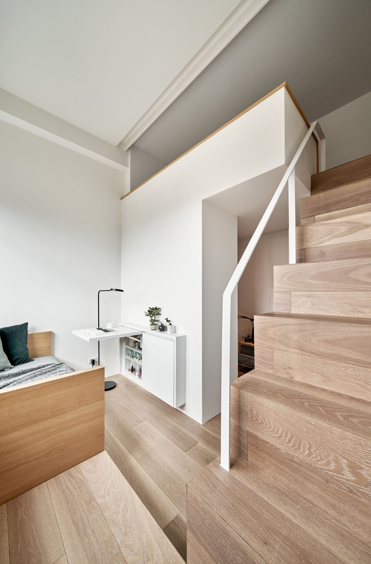 The living room is also the dressing and includes a built-in shoe cabinet and a fold-down desk