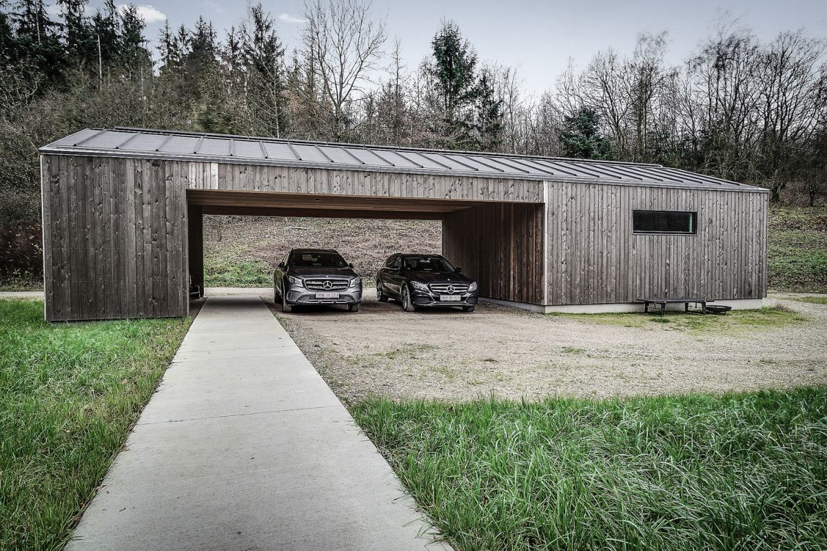 The carport acts as a privacy shield, a barrier between the house and the trail