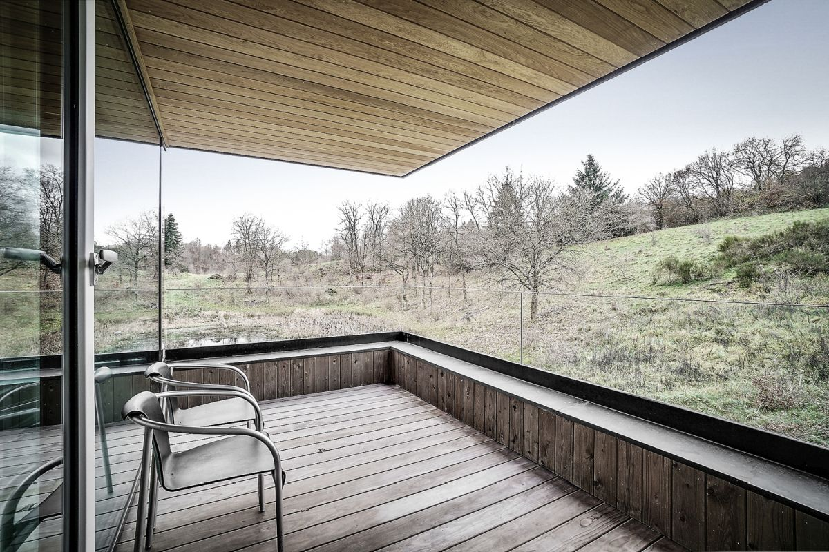 Glass doors connect the living spaces to a covered terrace with panoramic views of the surroundings