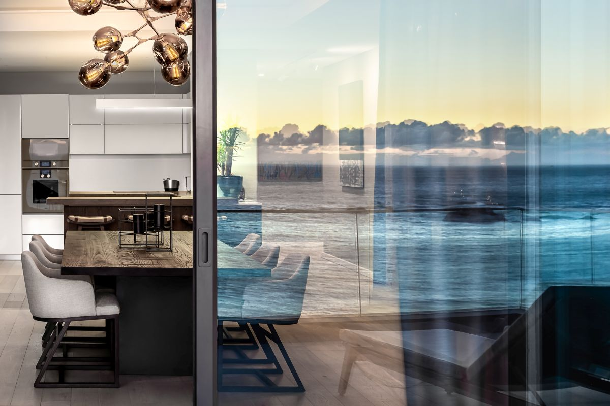 Sliding glass doors divide the indoor and outdoor spaces yet maintain the visual connection between them