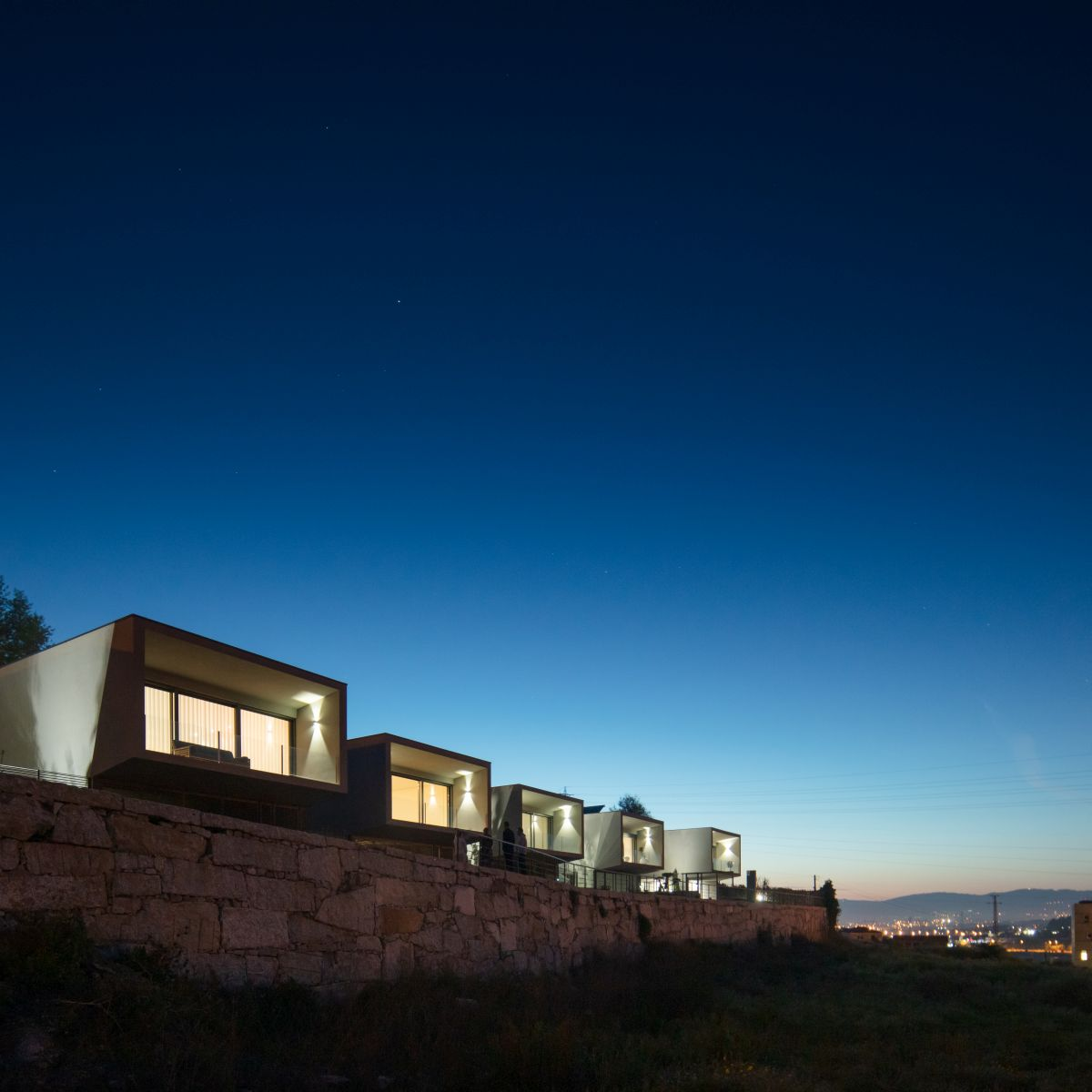 The development is framed by a stone wall which stretches all around it