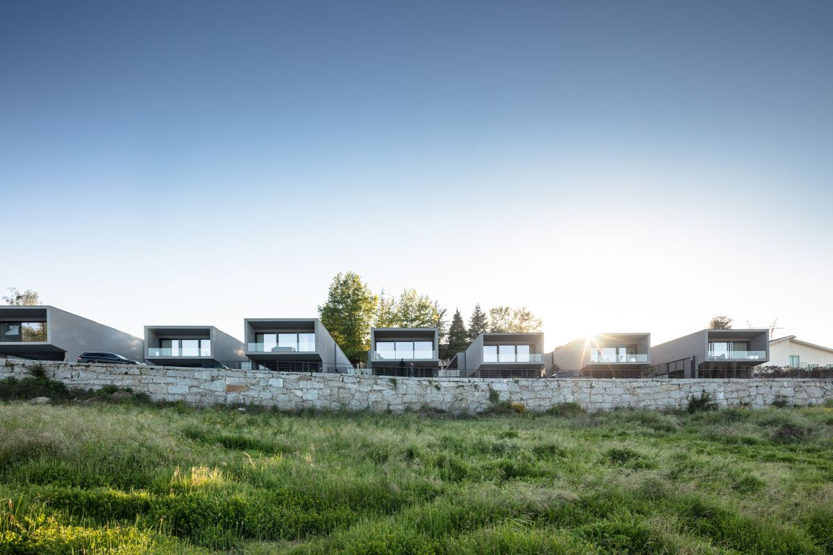 All seven houses are lined up, oriented towards the view and parallel to each other