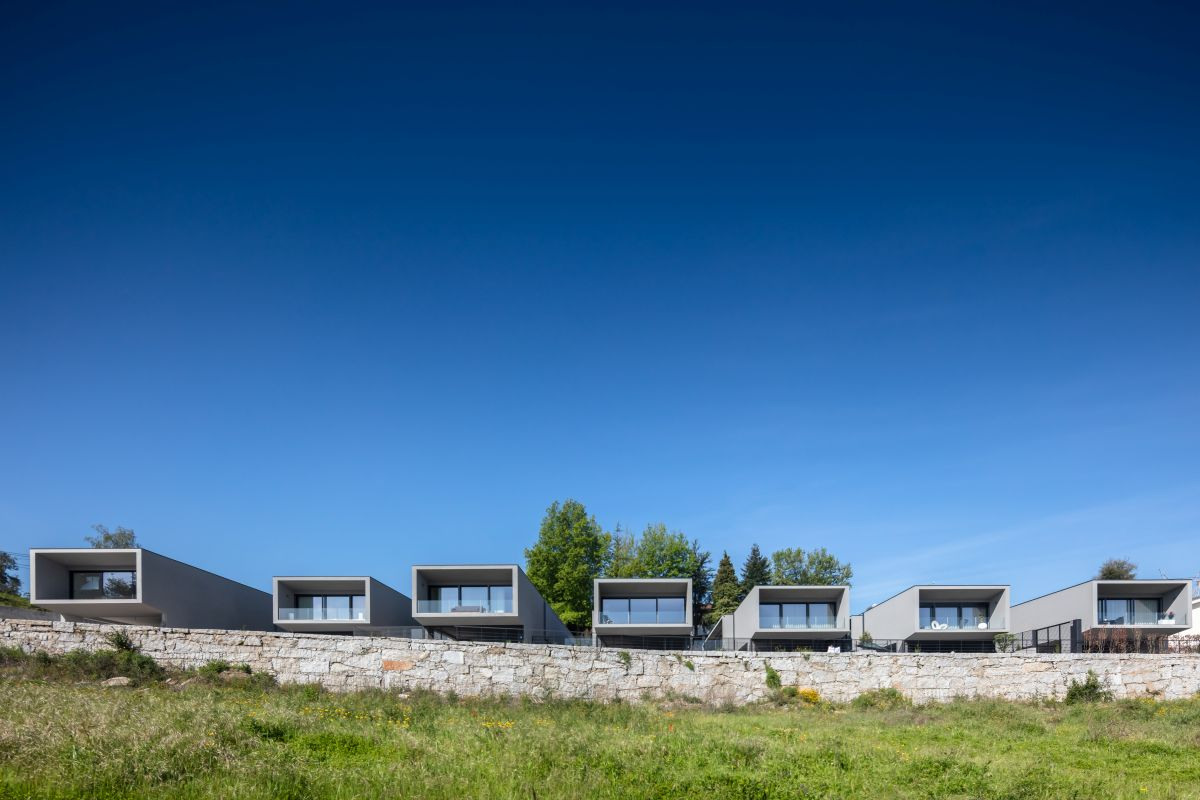 The houses are all parallel to each other and oriented towards the open land in the distance