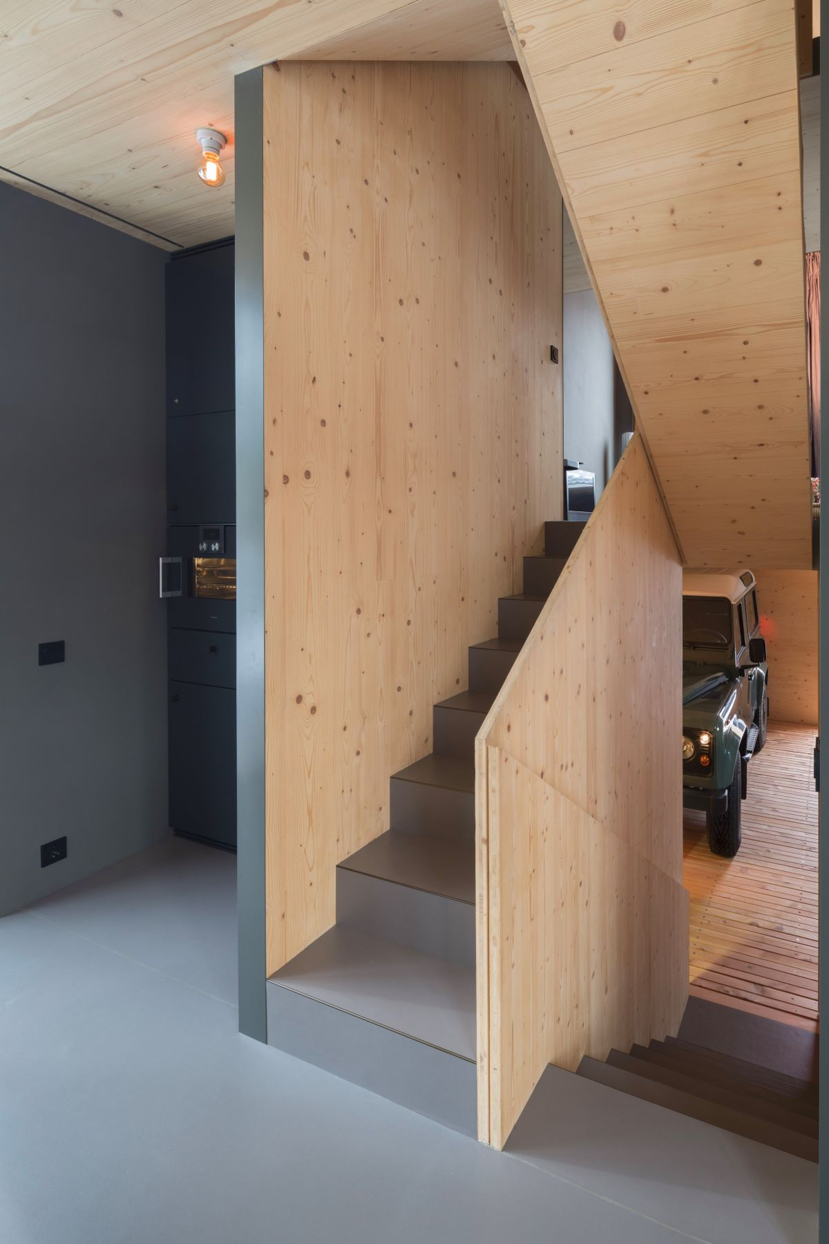 The staircase which connects the floors is very simple and framed by wood panels on either side