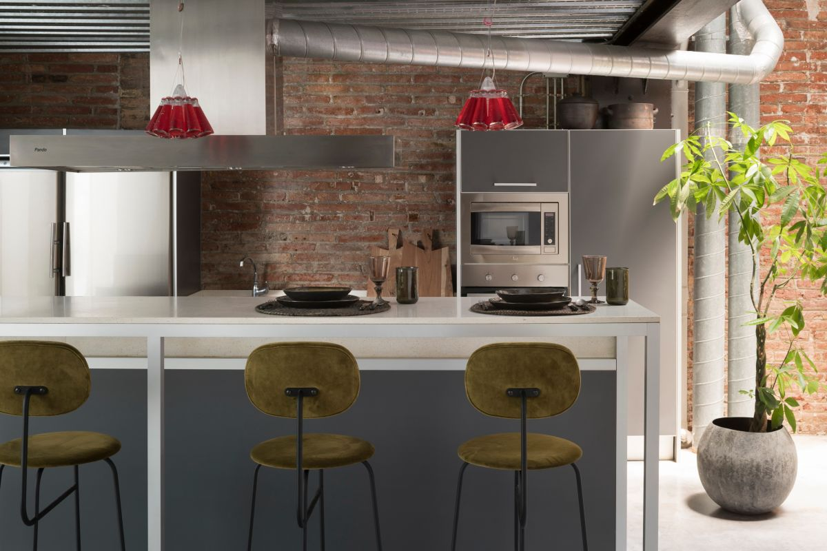 The kitchen features subdued colors and simple materials and has a modern-industrial vibe