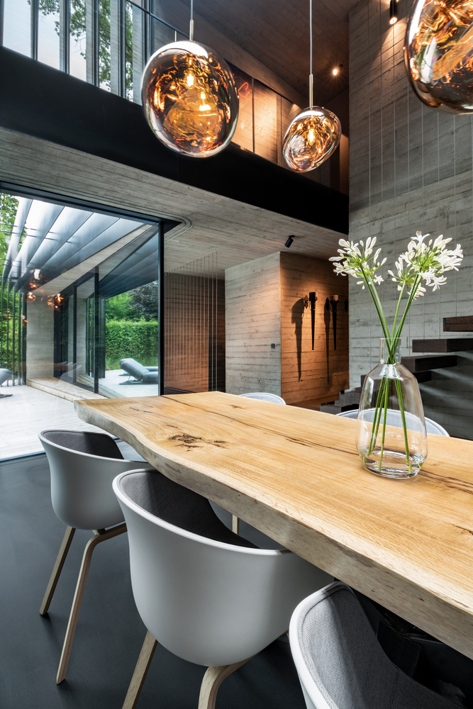 The live edge dining table softens the harsh exposed concrete surfaces, adding warmth to the ground floor