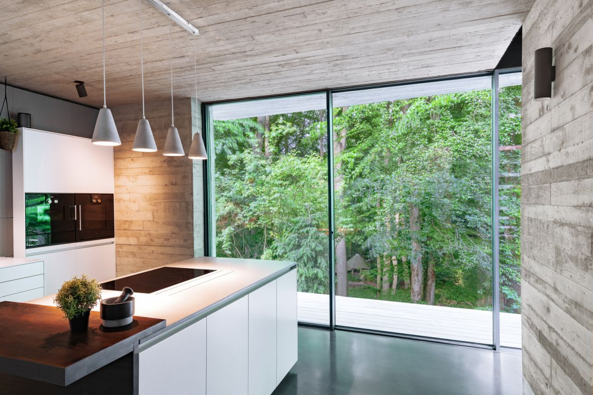 The minimalist kitchen opens up to the forest, featuring glass surfaces that let lots of light inside