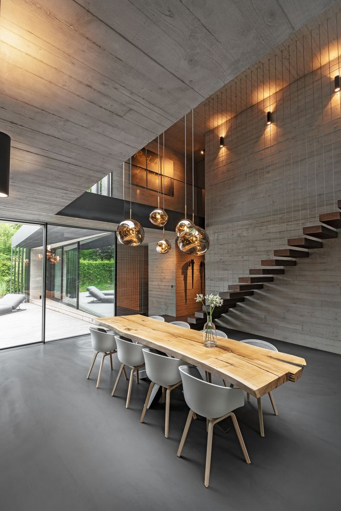 A minimalist staircase appears to be floating against the dining room wall, connecting the two floors