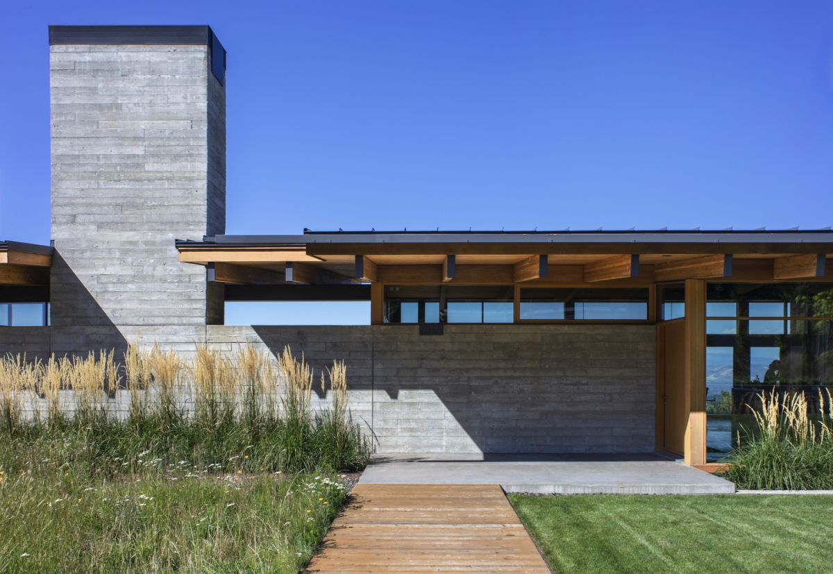 The concrete wall also incorporates a tall chimney for the central fireplace