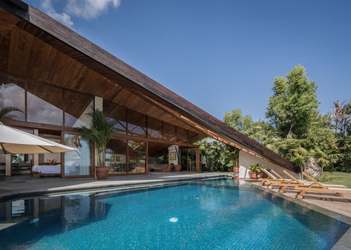 The living areas open up to a covered patio and a swimming pool, partially covered by the unique roof