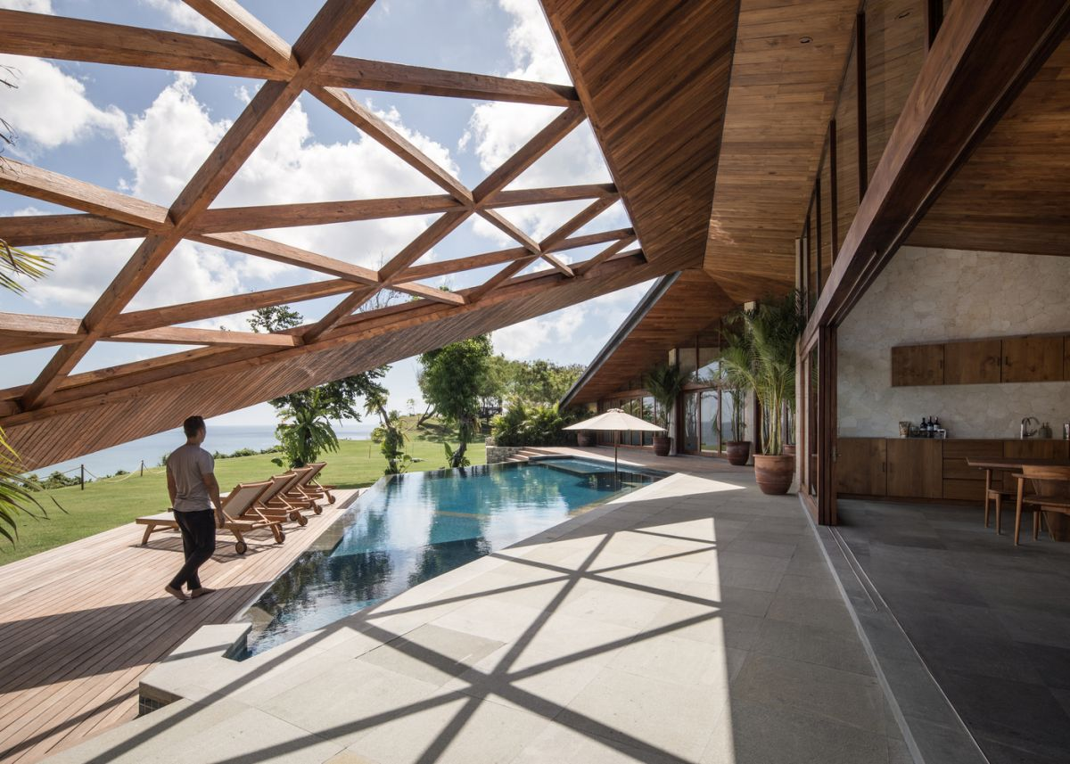 The roof extends over the poolside area, forming an unusual decorative cover