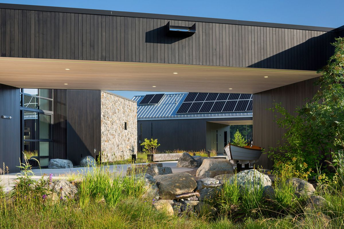 On the outside the house is clad in dark stained cedar wood and in stone, both locally-sourced