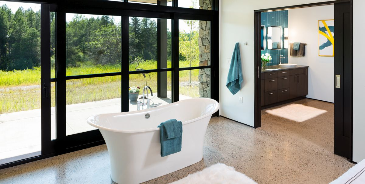 The freestanding tub is placed outside the bathroom, where it can take advantage of the scenery
