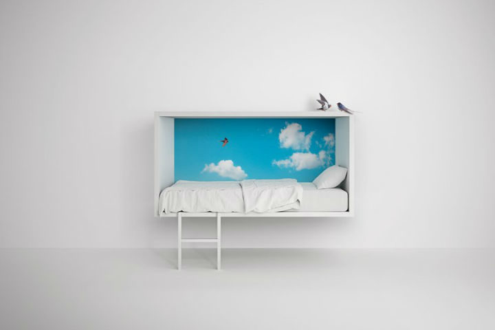 zoomed out image of a bed with sky painting for children