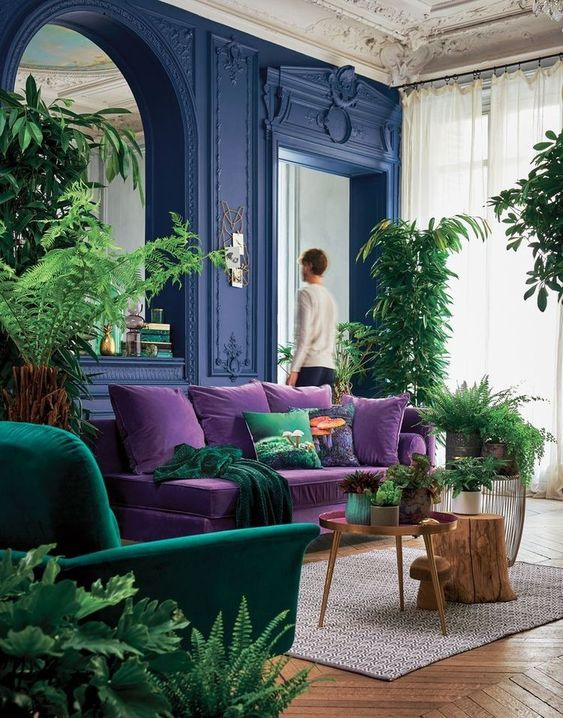 living room with velvet purse sofa and green armchair