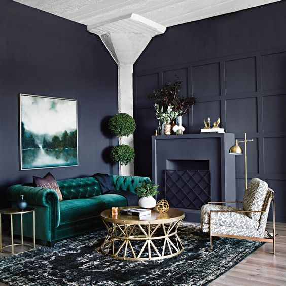 living room with green velvet sofa and black walls
