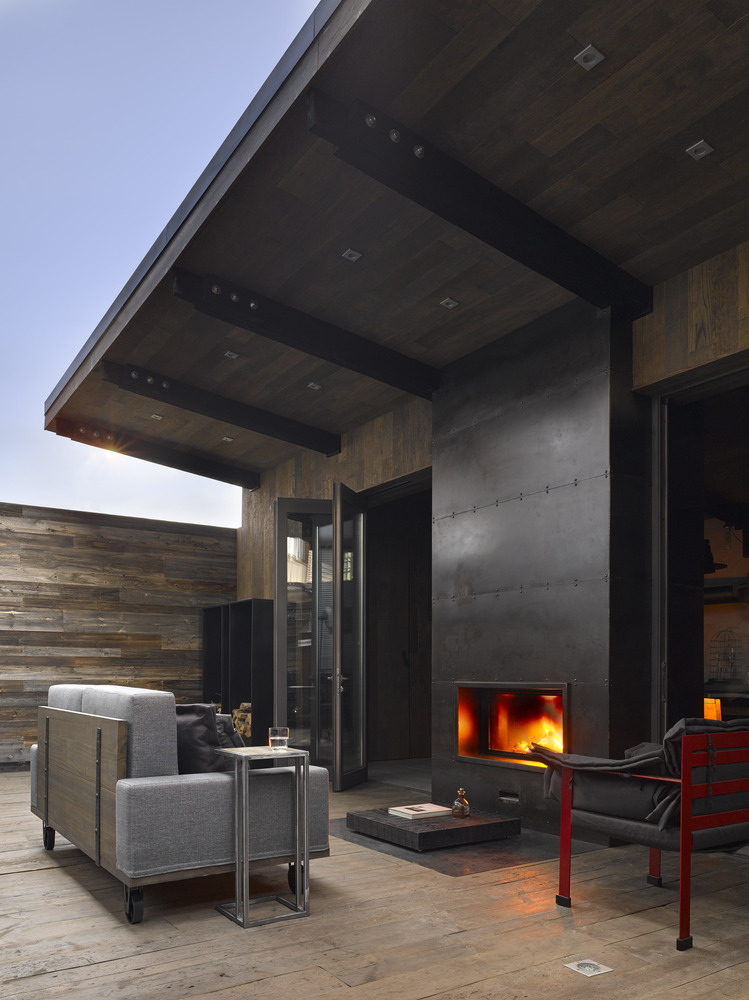 The fireplace is double-sided and the roof overhang creates a cozy protected area outside