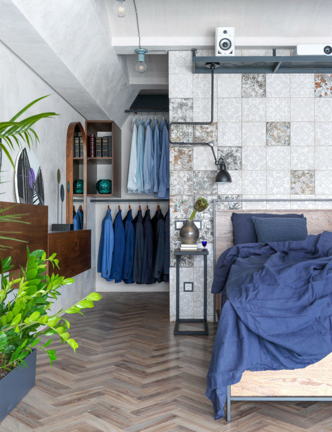 loft bedroom with wood flooring open wardrobe and stucco on walls and ceilings
