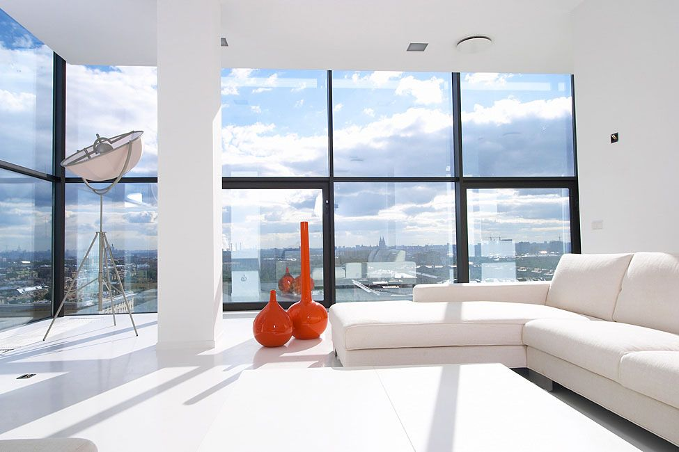 The all-white walls, sofa and flooring combined with the large windows give this living room a very pure and airy look