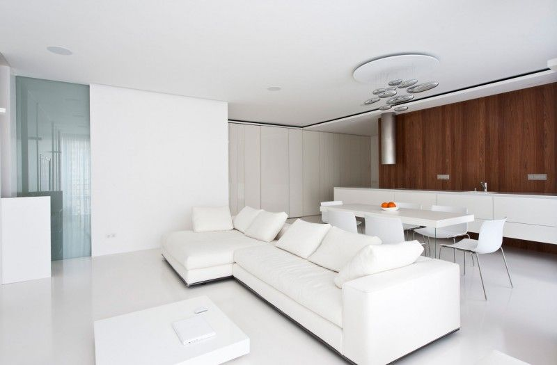 The white living room furniture is complemented here by wood paneling on the accent wall