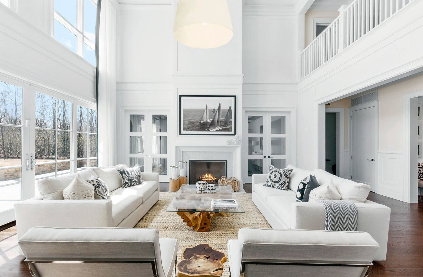 This double-height living room is furnished with two comfortable white sofas and matching armchairs, featuring a beach-inspired decor