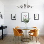 Delightful modern dining room with round white and gold dining table and four yellow chairs 71314 150x150 - Black, White and Brilliant Pops of Yellow Revitalize Old Epsom Apartment
